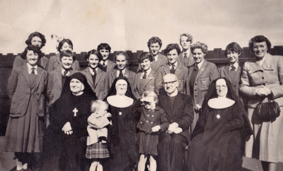 Joan Enright (née Dawson), standing right, and her Kilbride Convent senior class pose with the Parish Priest, nuns and Joan's young daughters, 1956.