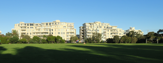 Lagoon Reserve with afternoon shadows cast across the ground with sunlit apartments in the background.