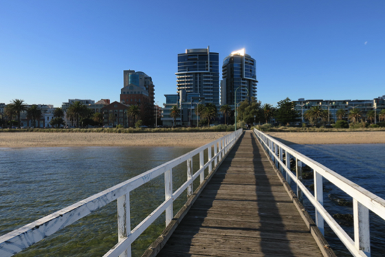 Colour photograph looking along a narrow pier towards the foreshore and the highrise HMAS Apartments.