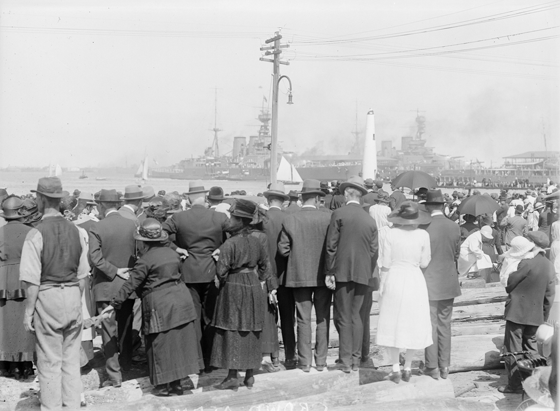 Shows crowd viewed from behind, ship in the distance.