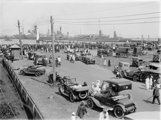 Shows shoreline crowded with onlookers and vehicles with ships in the distance.